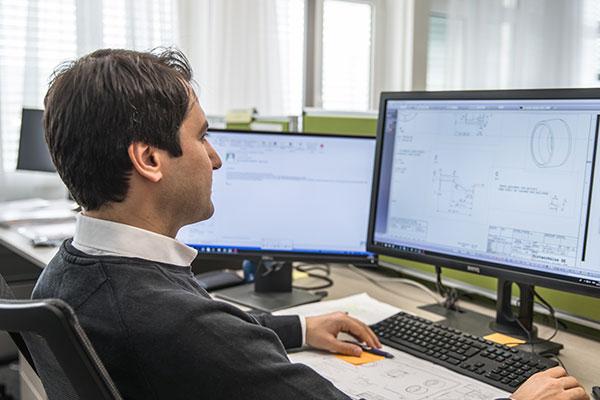 TSA Mitarbeiter vor dem Computer am Arbeitsplatz sitzend
